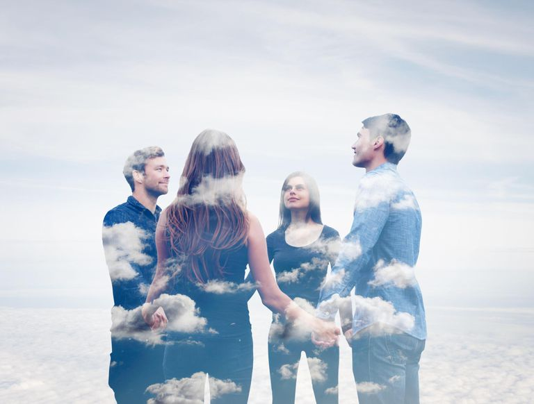 Four friends holding hands with clouds.