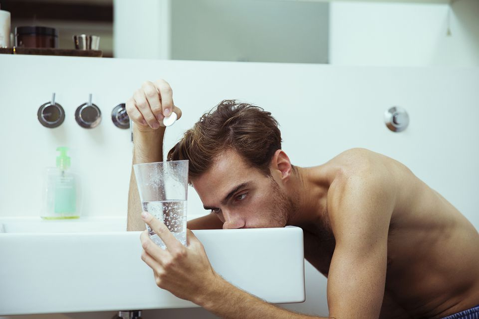 Hungover man watching effervescent tablets in bathroom
