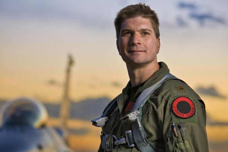A F-16 pilot holds a helmet in front of F-16 jet.