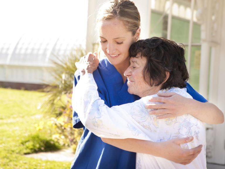 Young female nurse and senior woman embracing