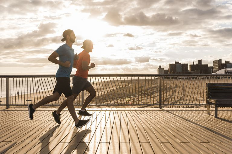 Two men running on the board walk