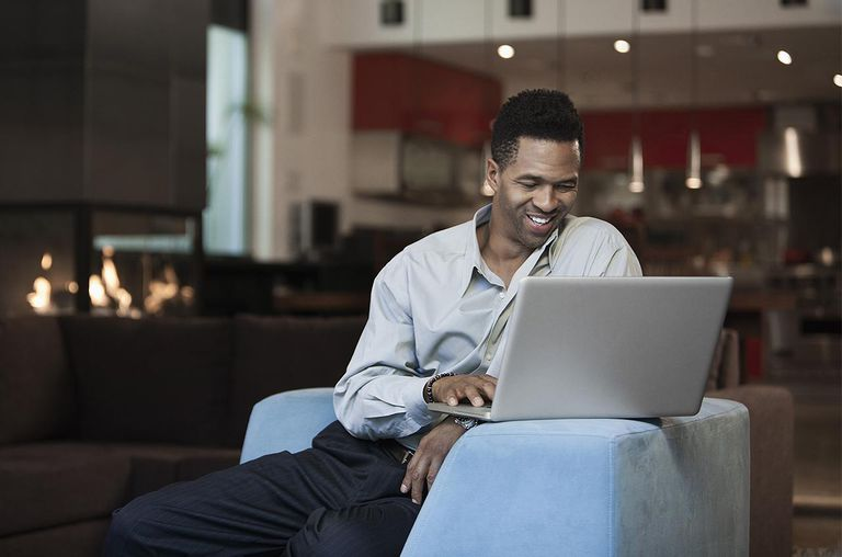 Mixed race businessman using laptop in living room
