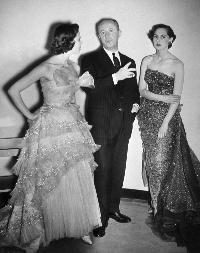 Fashion designer Christian Dior with two models wearing his creations.