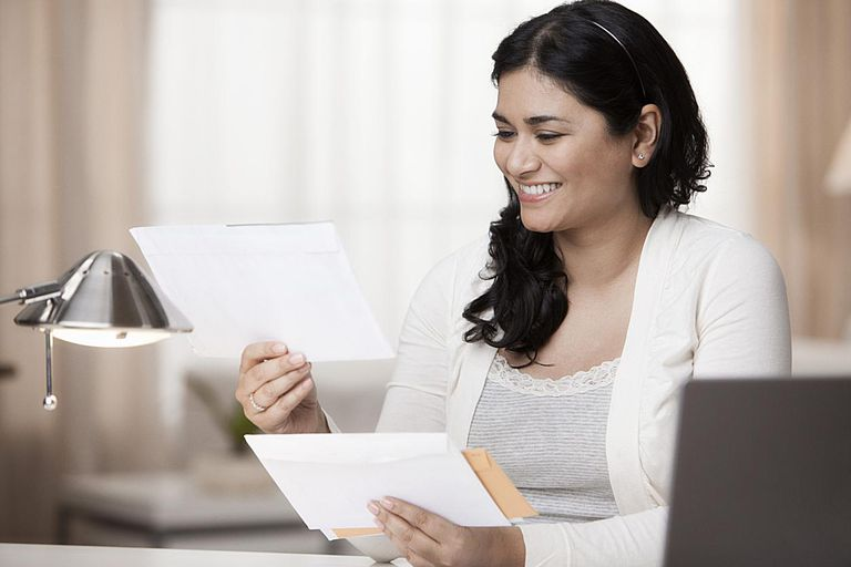 Young woman smiling as she opens a fundraising letter.