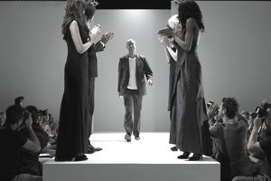 People applauding fashion designer on catwalk