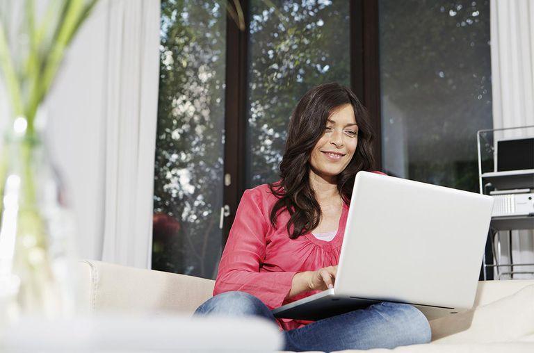 Woman using laptop on sofa, smiling, portrait