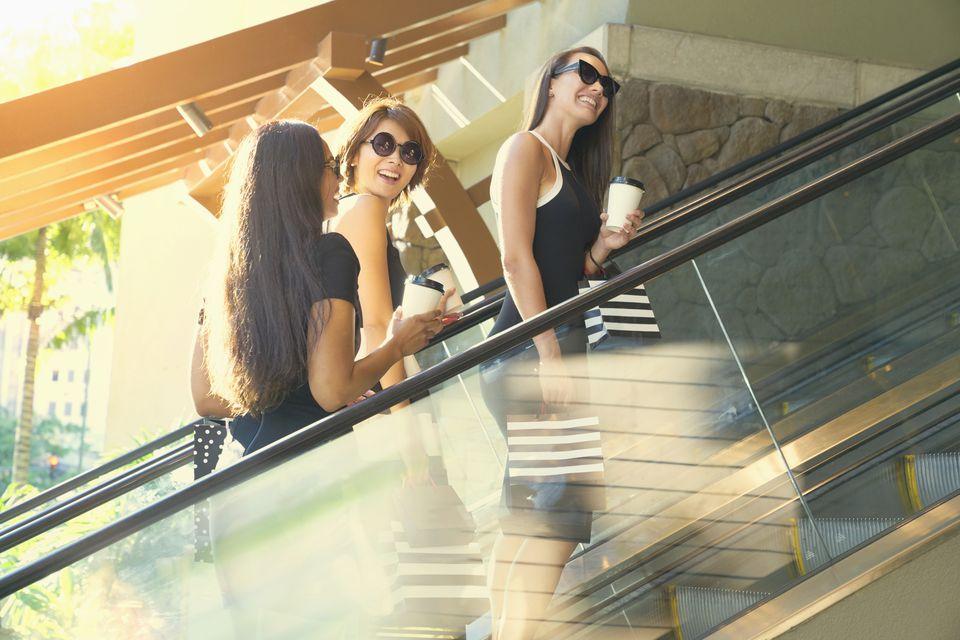 Glamorous friends riding escalator in shopping mall
