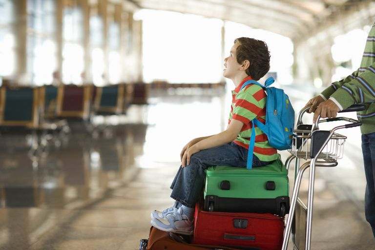 Niño sentado sobre maletas en aeropuerto