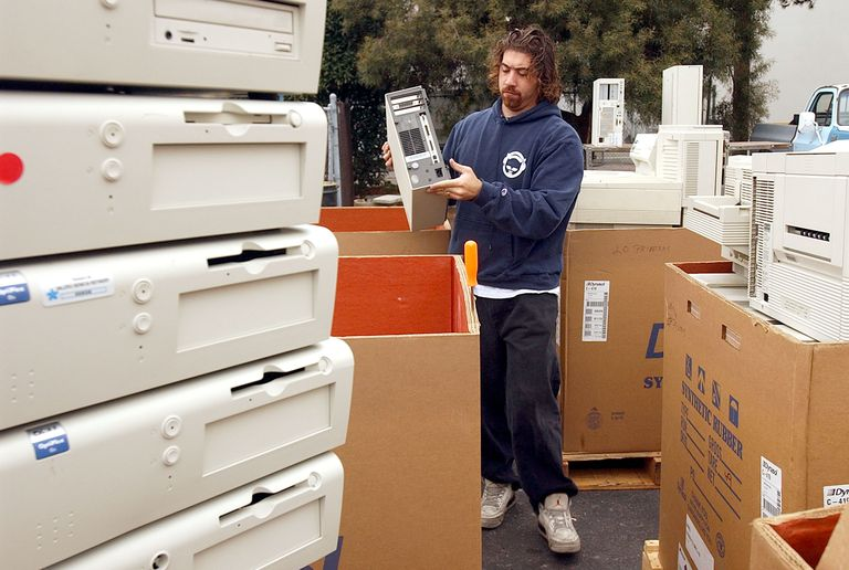 Man sorting old computer systems for recycling