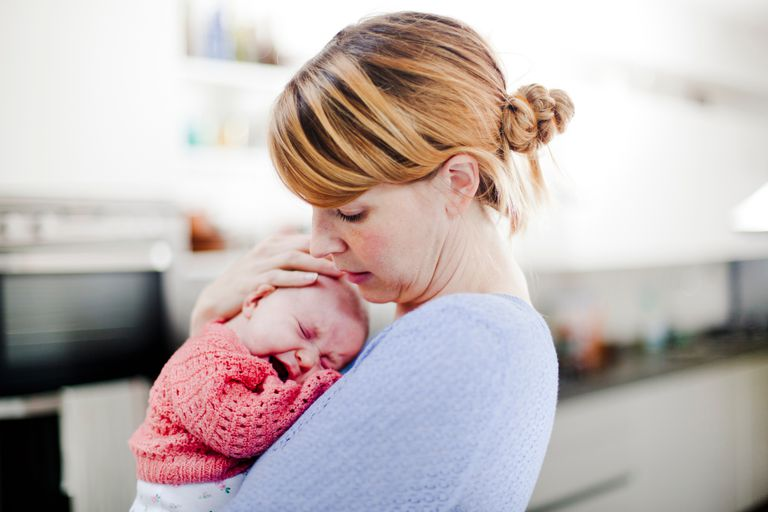 Mother holding newborn daughter