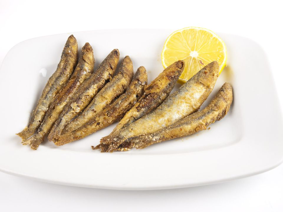 A plate of fried anchovies with a lemon