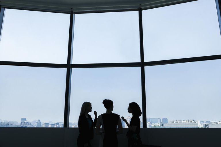 Silhouettes of three businesswoman in an office