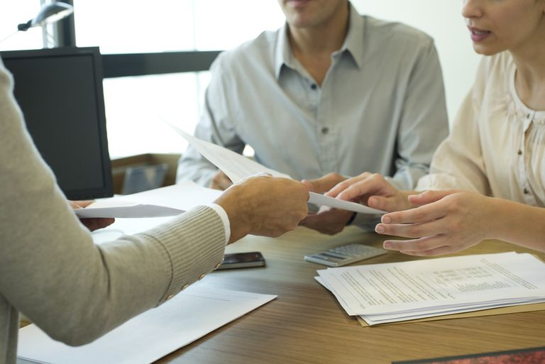 couple being handed paperwork across table