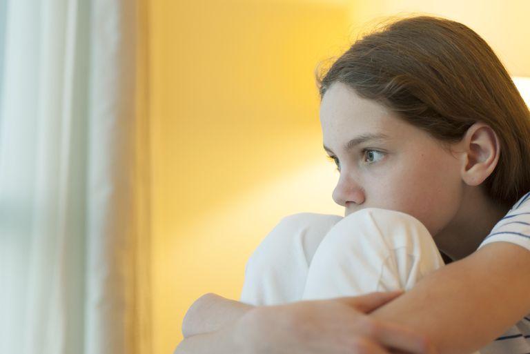 Preteen girl hugging knees, looking away in thought
