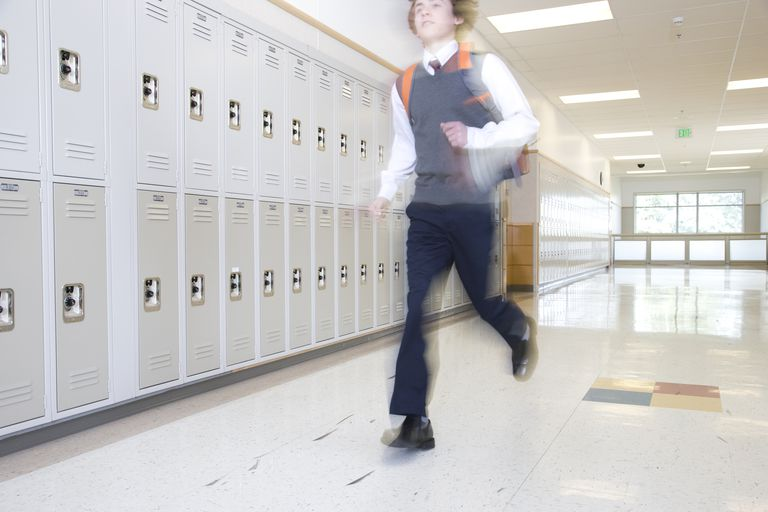 School boy (16-17) running past lockers in corridor