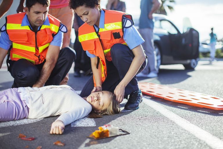 first responders checking unconscious girl