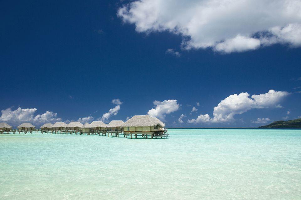 Resort huts built over tropical ocean