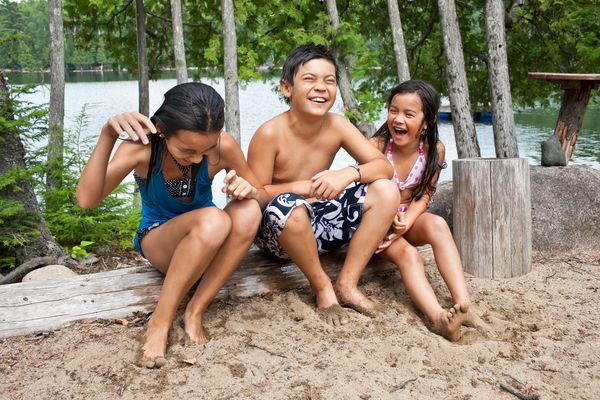Kids laughing by the lake at camp