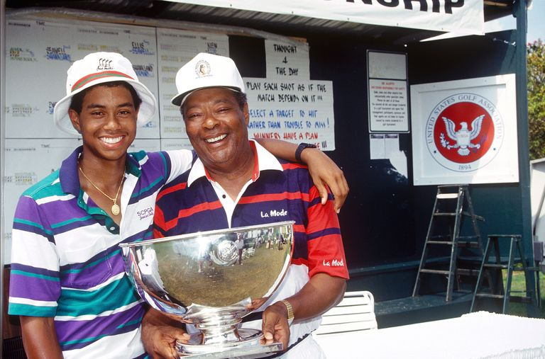 Tiger Woods, age 15 years, six months, and 28 days, and father Earl Woods, pose for a photo while celebrating Tiger's victory at the 1991 USGA Junior Amateur Championships on July 28, 1991