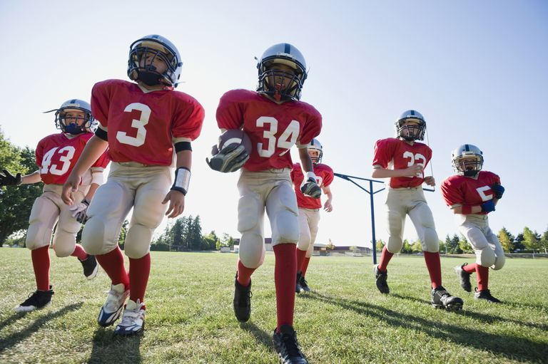 Kids in football uniforms running onto the field