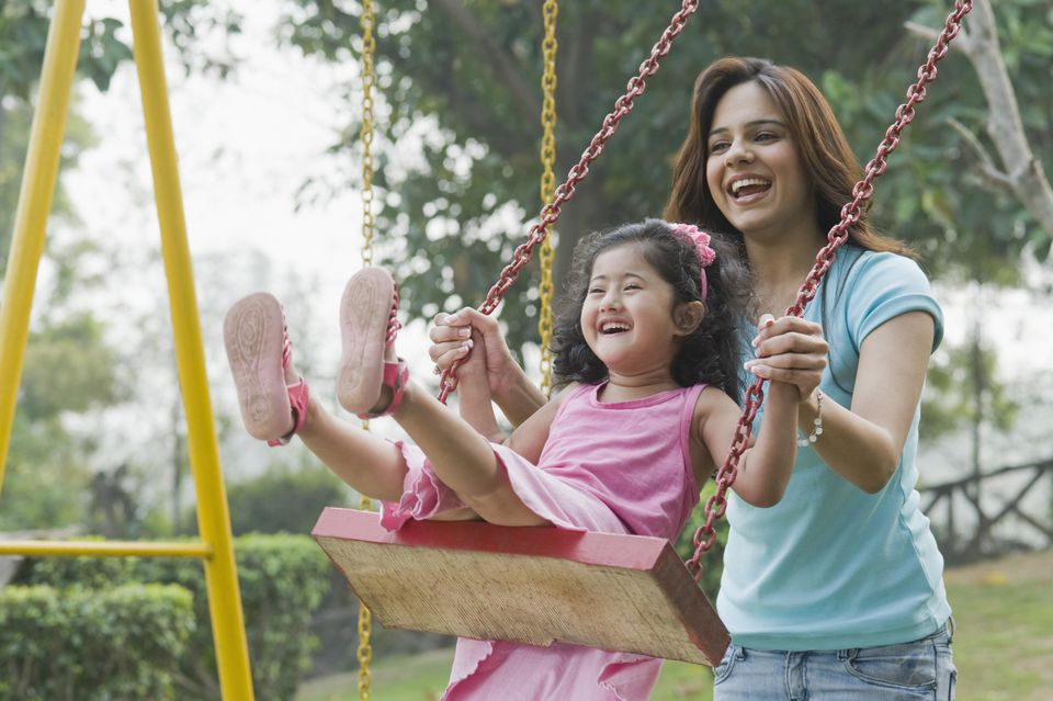 Woman pushing her daughter on a chain swing