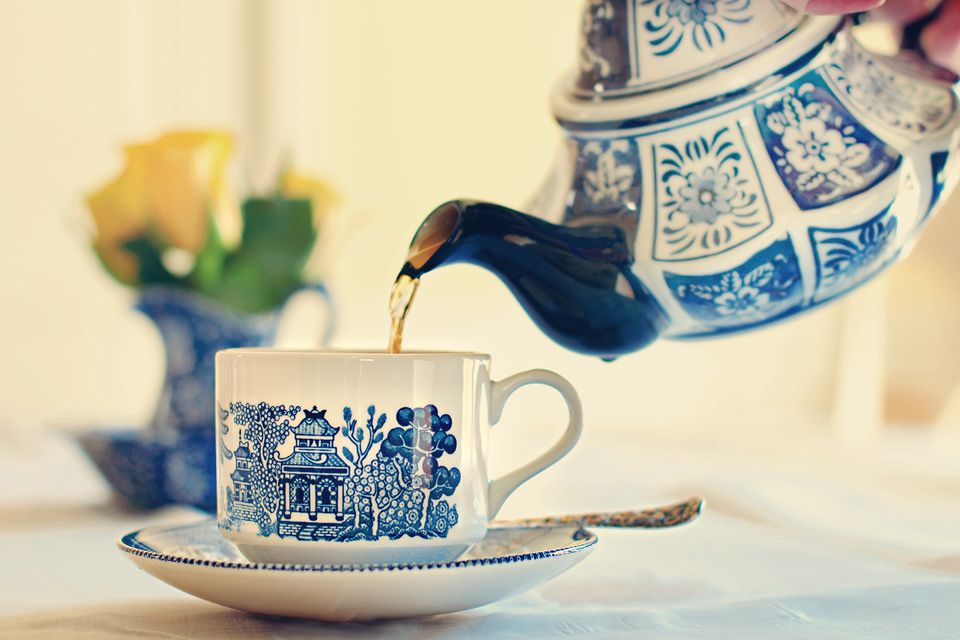 Blue and white china teapot pouring tea into china tea cup.
