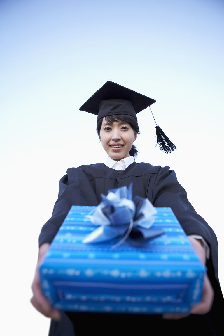 Close-up of teenage girl with mortar board holding gift