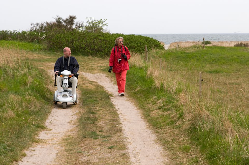 A man on a mobility scooter and a walking woman explore a seaside nature trail.