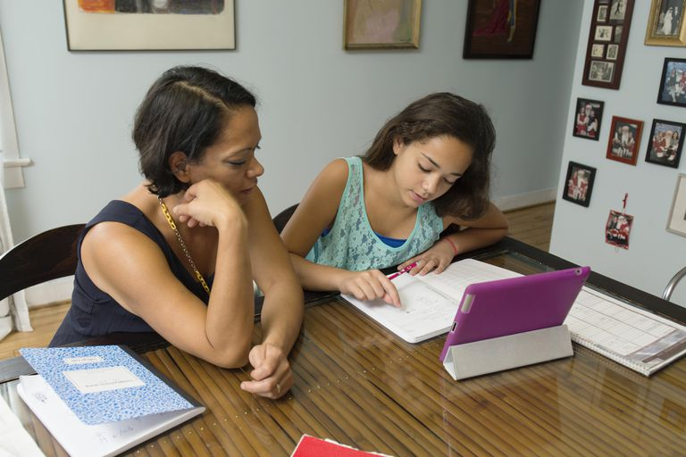 Mixed race mother helping daughter with homework