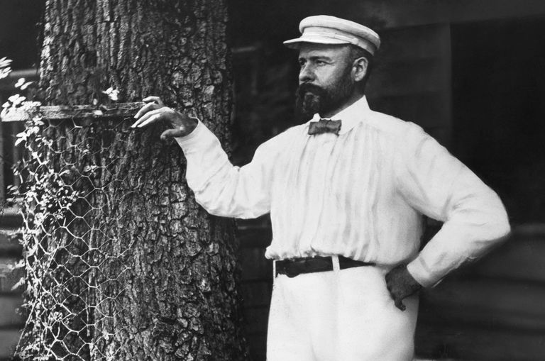 Black and white photo of bearded Louis Sullivan leaning on a tree