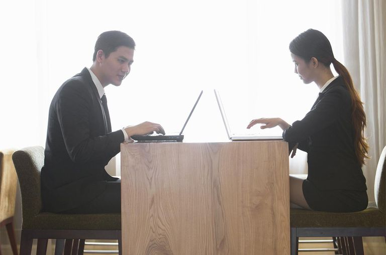 Two people having a business meeting with laptops