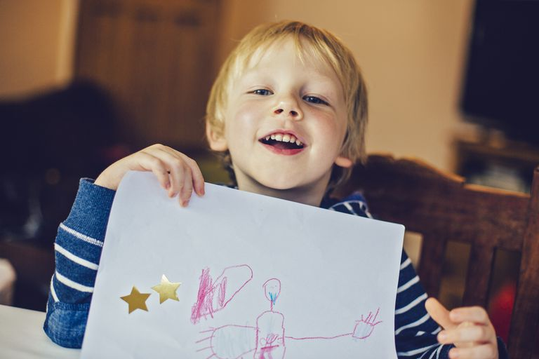 self esteem - boy smiling and proud holding up picture