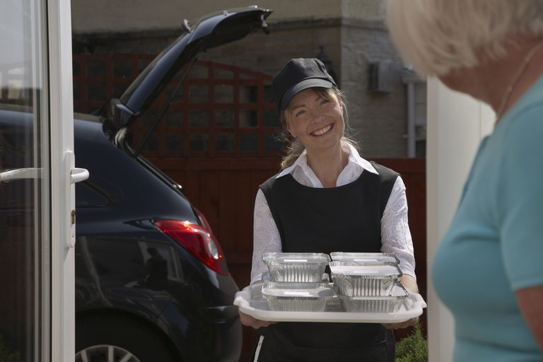 A volunteer delivering meals to the elderly.