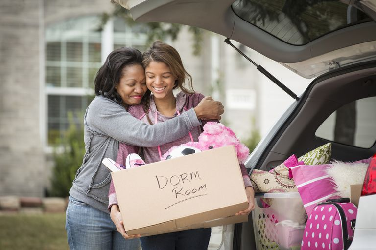 African American mother helping daughter pack for college