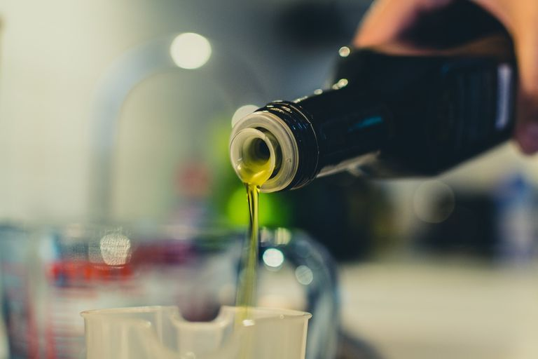 Cropped Image Of Woman Pouring Vegetable Oil In Jar