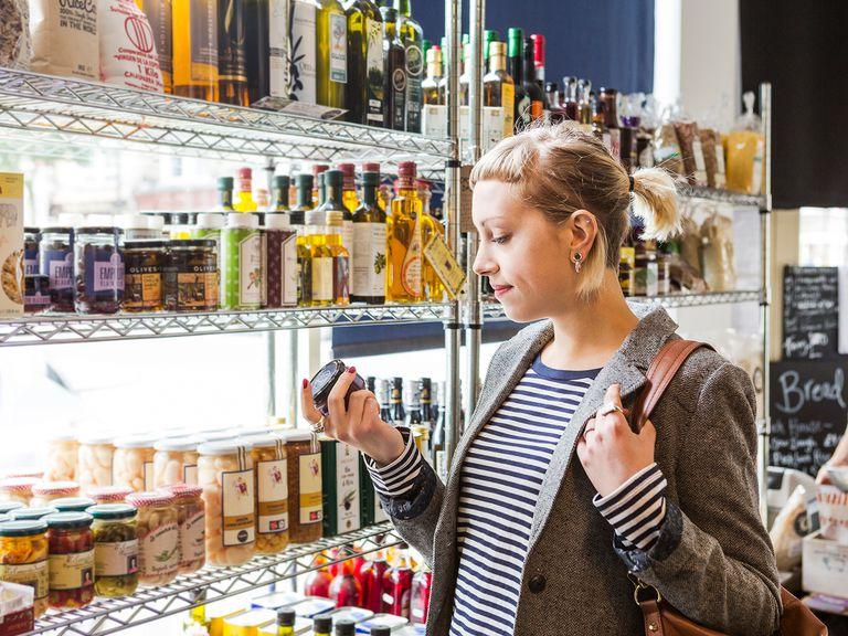 Female shopper reads label of jar in shop.