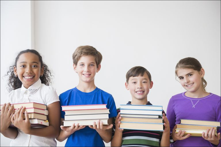 Photo of four smiling children holding books