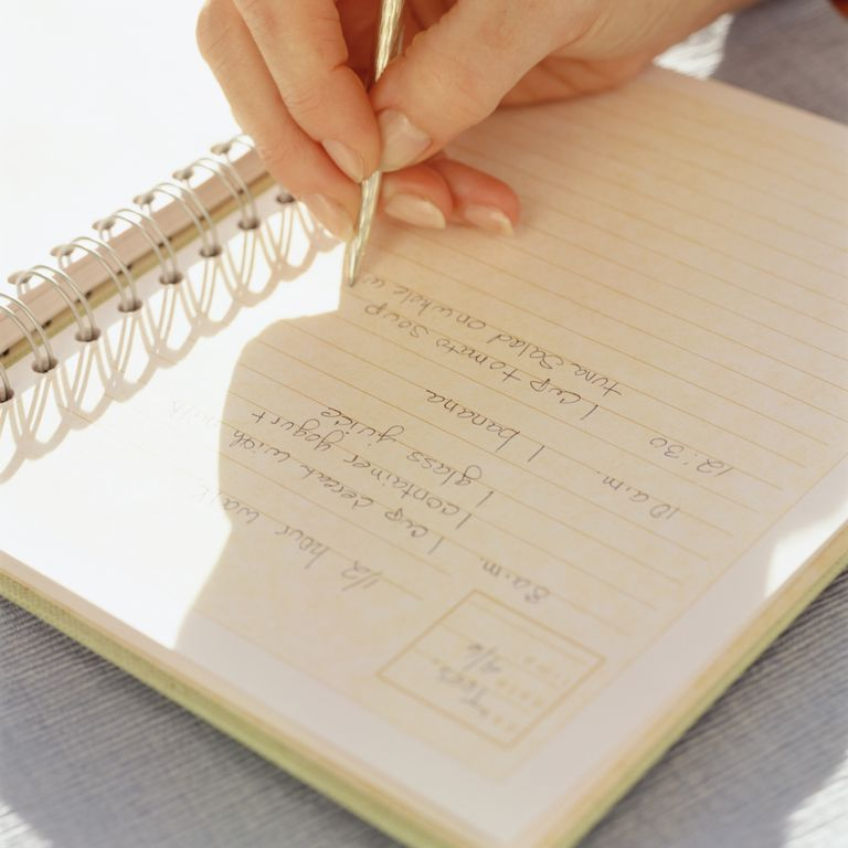 Hand writing a recipe in a notebook for a cookbook