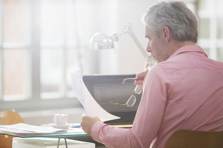 mature man looking at paperwork in front of laptop