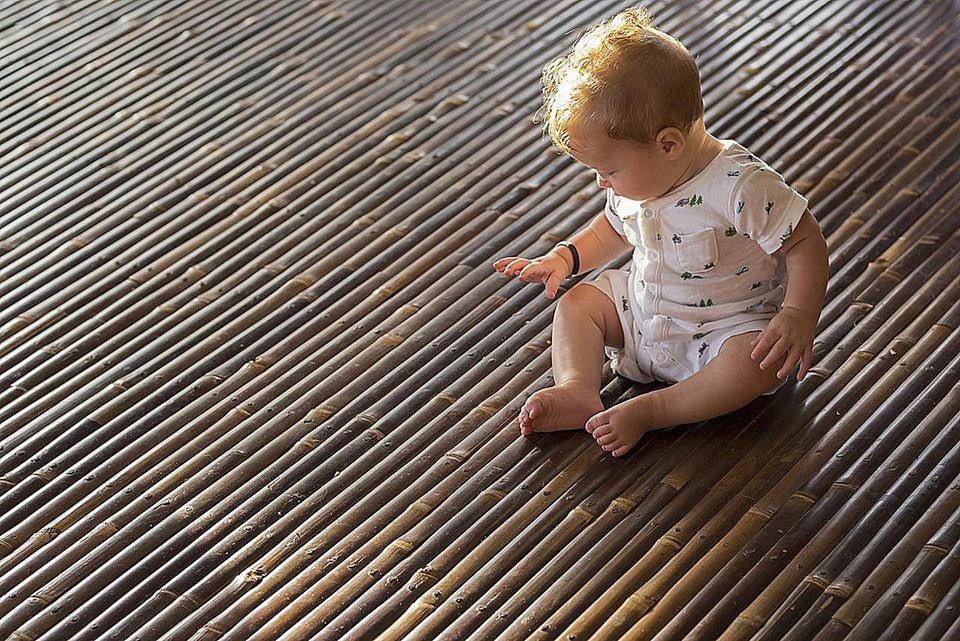 Caucasian baby playing on bamboo floor