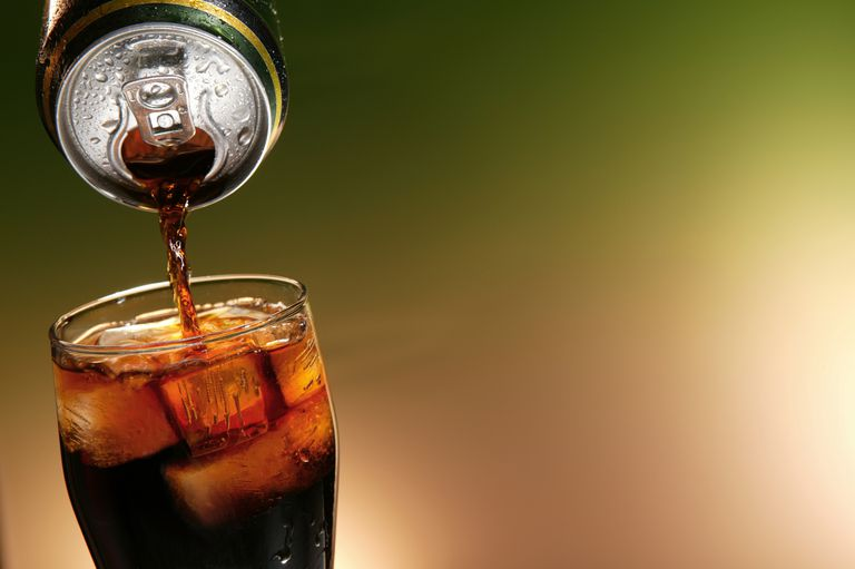 cola can pouring in a glass