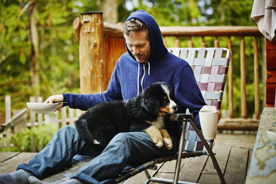 Man sitting in chair with puppy sitting on lap