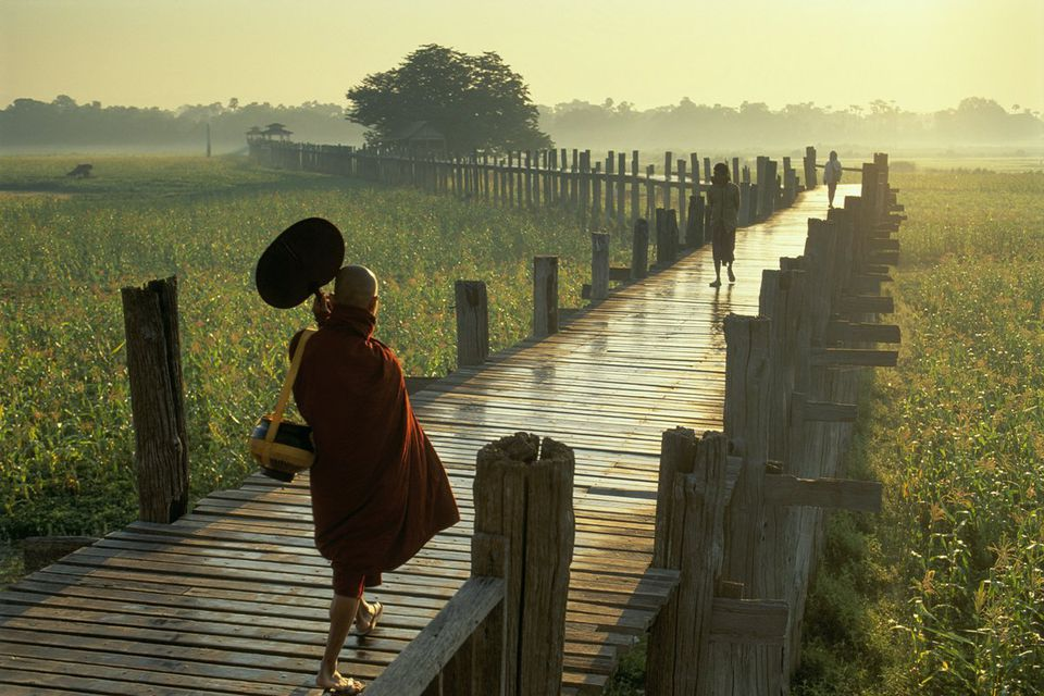 Monk crosses U Bein Bridge near Mandalay, Myanmar.