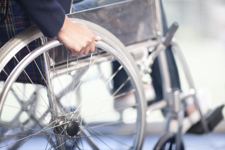 close up of woman's hand on wheel of wheelchair