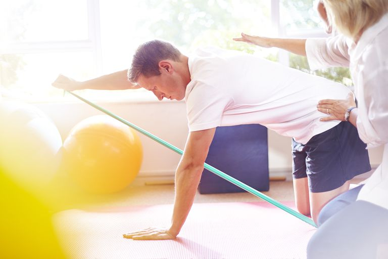 Physical therapist guiding man pulling resistance band