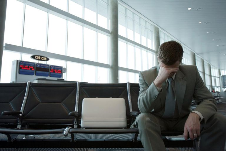 Businessman sitting in airport lounge, holding head