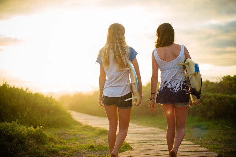 Two girls walking to the beach with surfboards