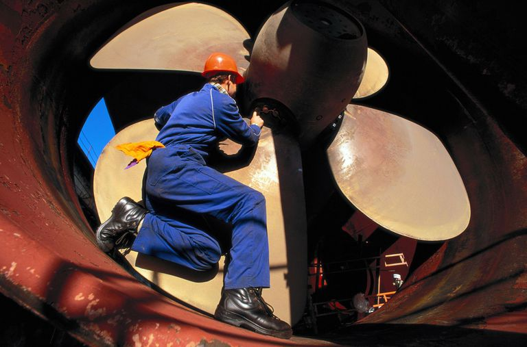 Man in Hardhat Inspects Large Ship Propeller in Thrust Tunnel