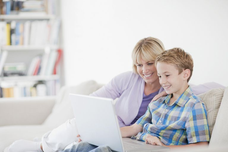 Mother and son using laptop together on sofa