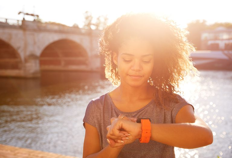 woman looking at watch next to river